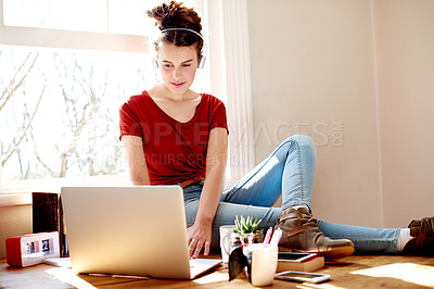 Buy stock photo Shot of a teenage girl listening to music on her laptop