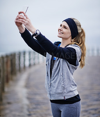 Buy stock photo Shot of a young woman taking a selfie while exercising outdoors