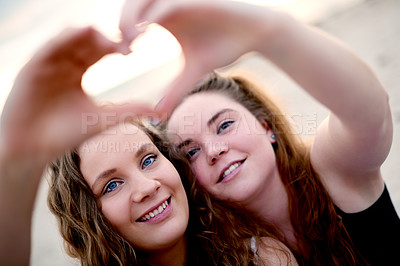 Buy stock photo Closeup shot of two friends making a heart shape with their hands