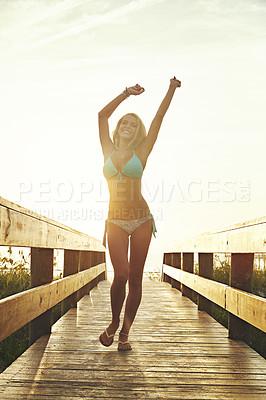 Buy stock photo Shot of a young woman in a bikini on a walkway near the beach