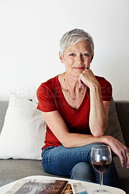 Buy stock photo Portrait of a mature woman sitting on her living room sofa drinking a glass of wine