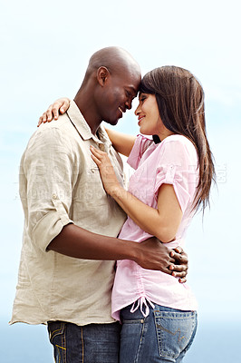 Buy stock photo Shot of an affectionate couple standing arm in arm outdoors
