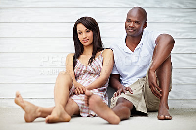 Buy stock photo Shot of a couple sitting outside leaning against a wall