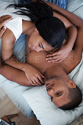 Buy stock photo High angle shot of a content young couple lying in bed