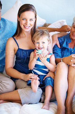 Buy stock photo Portrait of mother and son sitting on a sofa with family and smiling
