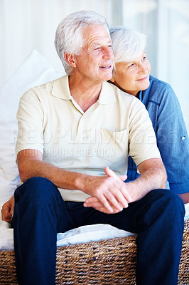 Buy stock photo Senior couple sitting together on a sofa and looking away