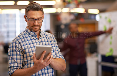 Buy stock photo Cropped shot of a mature businessman using a digital tablet in the office