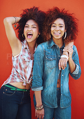 Buy stock photo Shot of two young friends posing against a red background