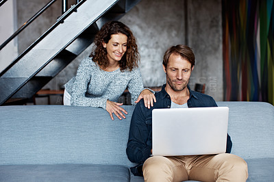 Buy stock photo Shot of a mature couple using a laptop in their living room