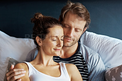 Buy stock photo Shot of an affectionate mature couple lying in bed together