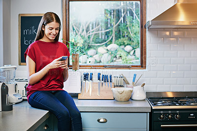 Buy stock photo Shot of a young woman sitting on her kitchen counter using a cellphone