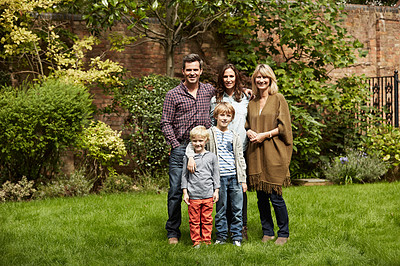 Buy stock photo Portrait of a multigenerational family standing in their backyard