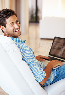 Buy stock photo Man sitting on a sofa using laptop and giving you an attractive smile