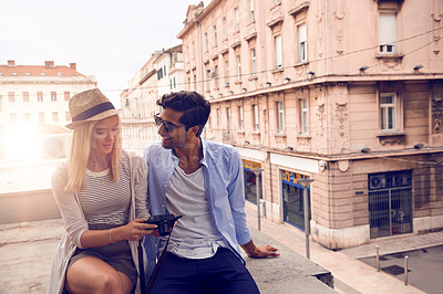 Buy stock photo Shot of a young couple looking at photos on their camera while out sightseeing in a foreign city
