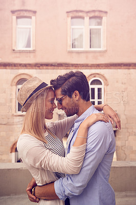 Buy stock photo Shot of a young couple embracing while touring a foreign city