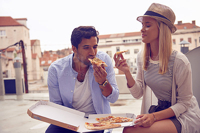 Buy stock photo Shot of a young couple having takeaway pizza while touring a foreign city