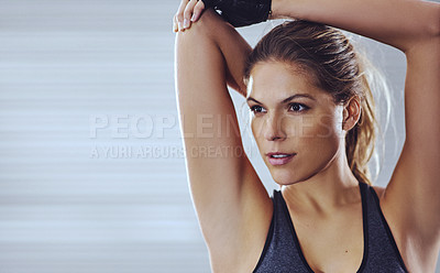 Buy stock photo Shot of a young woman stretching her arms before a gym workout