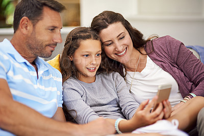 Buy stock photo Cropped shot of a family sitting on the sofa at home