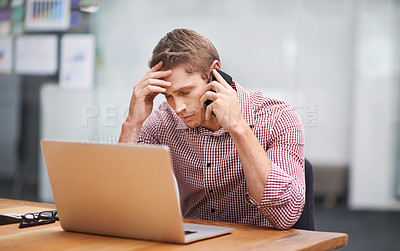 Buy stock photo Shot of a businessman talking on the phone while working on his office computer