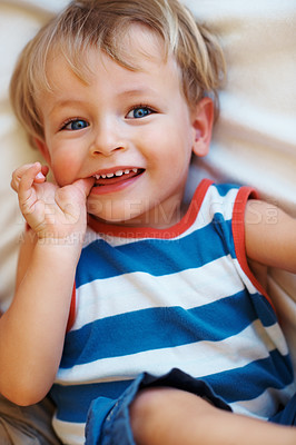 Buy stock photo Closeup portrait of smiling child with thumb in mouth lying on sofa