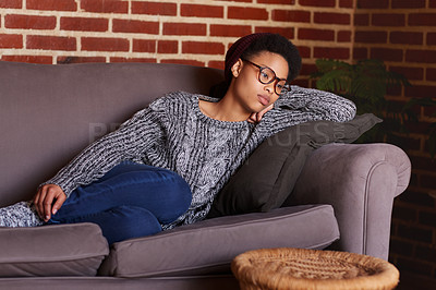 Buy stock photo Shot of a young woman looking thoughtful while relaxing at home