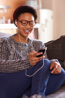 Buy stock photo Shot of a young woman listening to music through her earphones