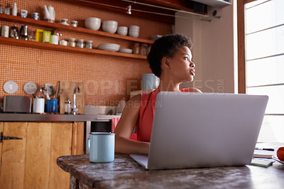 Buy stock photo Shot of a young woman working on a laptop in her kitchen
