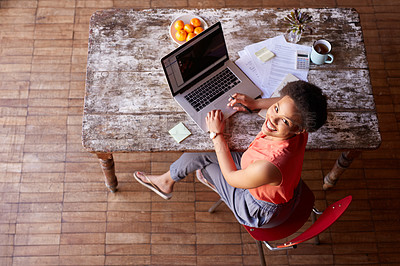 Buy stock photo High angle portrait of a young woman working on a laptop at her kitchen table