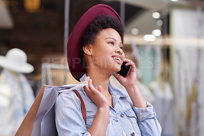 Buy stock photo Cropped shot of a young woman talking on her cellohone while shopping