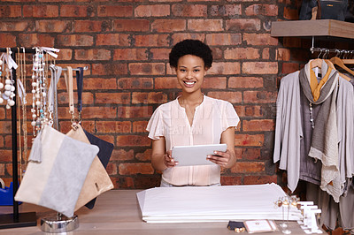 Buy stock photo Cropped portrait of a young woman using a tablet in her clothing boutique
