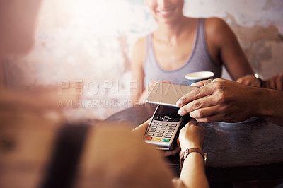 Buy stock photo Cropped shot of a customer paying for coffee with a smartphone at a cafe