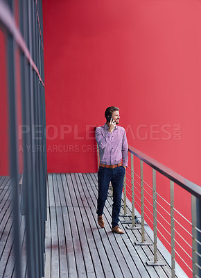 Buy stock photo Shot of a young businessman talking on a phone on the balcony of an office