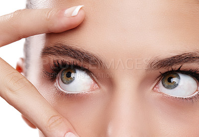 Buy stock photo Closeup studio shot of a beautiful young woman touching her face isolated on white