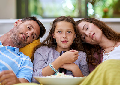 Buy stock photo Cropped shot of a young girl watching a movie while both her parents sleep on either side of her