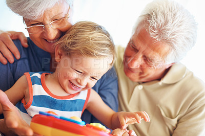 Buy stock photo Cute little boy playing with a toy with his grandparents