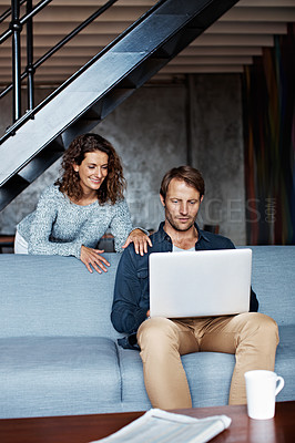 Buy stock photo Shot of a man sitting on the sofa using a laptop with his wife looking over his shoulder