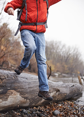 Buy stock photo Cropped shot of a hiker climbing over a tree trunk