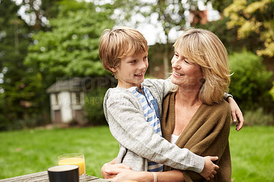 Buy stock photo Shot of a grandmother and her grandson hugging while sitting at a table in her yard