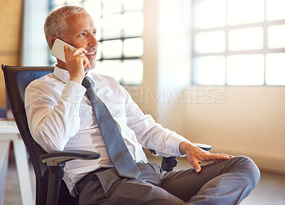 Buy stock photo Shot of a mature businessman using his phone in the office