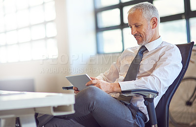 Buy stock photo Shot of a mature businessman using a digital tablet in an office