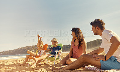 Buy stock photo Shot of a young family sitting on the beach