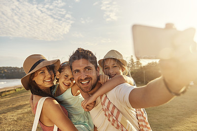 Buy stock photo Shot of a father taking a selfie with his family while out on the beach