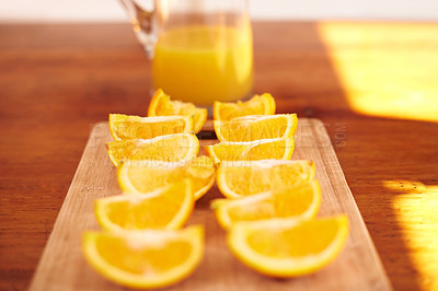 Buy stock photo Shot of orange quarters lined up on a chopping board in a kitchen