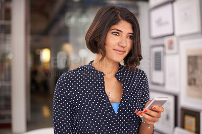 Buy stock photo Shot of a young woman using a mobile phone in an office