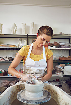 Buy stock photo Shot of a young woman making a ceramic pot in a workshop