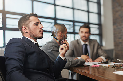 Buy stock photo Shot of a businessman smoking a pipe during a meeting at the office