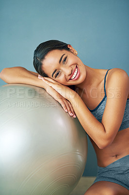 Buy stock photo Shot of a sporty young woman leaning against a pilates ball