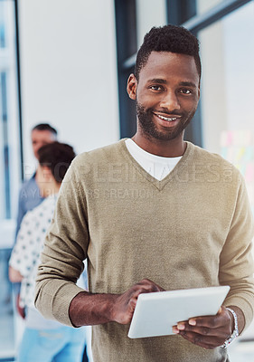 Buy stock photo Cropped portrait of a young businessman working in the office with her colleagues in the background