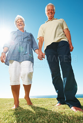 Buy stock photo Low angle view of smiling couple holding hands and standing on grass