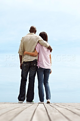 Buy stock photo Rearview shot of a young couple standing side by side on a boardwalk looking at the ocean